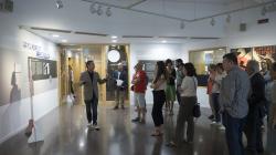 """Un grup de persones escolten atentament les explicacions del comissari de l'exposició """"Barcelona Coopera"""". La sala està decorada amb plafons i obres que formen part de l'exposició."""