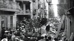Una multitud de persones es troben encallades al mig d'un carrer en ruïnes a causa d'un bombardeig aeri.