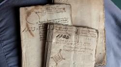 Tres llibres antics sobreposats entre si amb les cobertes manuscrites. A la coberta del llibre de primer pla s'observa el dibuix del senyal heràldic de la ciutat de Barcelona