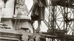 A la imatge s'observa com uns operaris estan preparant amb politges l'estàtua de Cristòfol Colom per pujar-la fins al capdamunt del monument dedicat a ell. A mà dreta trobem tota una estructura de ferro amb escales com a suport a la construcció general del monument i, a primer pla, apareix un operari amb una escala portable.