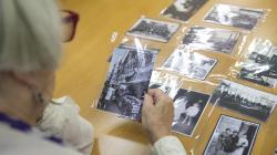 Una mujer mayor mira fotografías antiguas