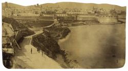 Imatge de Barcelona de mitjans del segle XIX on s'observen les muralles que ressegueixen el contorn de la ciutat primigènia, la qual s'obre al mar. A primer pla apareixen les figures de tres persones mentre passegen arran de costa.