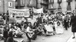 Tot un grup força nombrós de nens, asseguts al mig de la plaça de Sant Jaume, sostenen pancartes amb lemes a favor de l'escola pública. Una nena a primer pla està tocant una guitarra i altres nens duen les pancartes manuscrites penjades del coll.