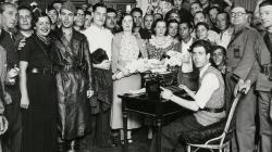 Un grup força nombrós de persones envolten les tres parelles que es casen al mateix moment, davant d'un secretari assegut que escriu a màquina. Tothom mira a càmera per a la foto.