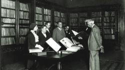 Fotografia en blanc i negre que mostra una sala amb prestatgeries plenes de llibres i una taula amb llibres exposats, en la qual diverses persones a una banda de la taula miren dues persones que estan contemplant un llibre.