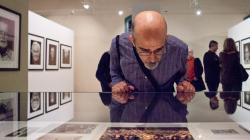 Un hombre observa atentamente una fotografía de una exposición, ligeramente apoyado en  una vitrina