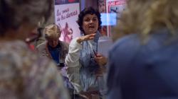 Una mujer, de cara a la cámara, da una explicación a otras mujeres colocadas en círculo a su alrededor y de espaldas a la cámara