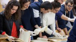 Un grupo de jóvenes observan documentos de archivo