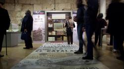 En una sala con vitrinas y plafones, varias personas observan los documentos expuestos