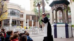 Un grupo de niños escucha las explicaciones de una monitora caracterizada como criada del siglo XIX como parte de una visita teatralizada