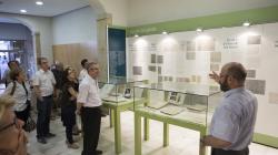 """Un grup de persones escolten atentament les explicacions del comissari de l'exposició """"Puig i Cadafalch, convertir Barcelona en la Brussel·les del migdia"""". La sala està decorada amb plafons i vitrines amb documents que formen part de l'exposició."""