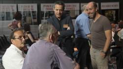 """4 homes conversen animadament entre ells a l'arribada a la jornada """"Reptes i oportunitats de la recerca local a Barcelona"""". Al fons s'observen plafons explicatius sobre la temàtica de la jornada."""