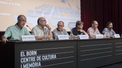 """6 ponents, amb els seus respectius cartells identificatius i micròfons, es troben asseguts en una taula presidencial allargada on hi ha escrit """"El Born Centre de Cultura i Memòria"""". Al seu darrere hi ha situada una pantalla on es projecten les presentacions de cadascun dels ponents."""