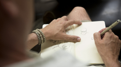 Una mano masculina que sostiene una libreta de apuntes de dibujo mientras la otra dibuja