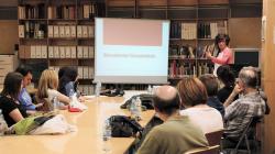"""11 persones assegudes als dos costats d'una taula allargada escolten atentament les explicacions d'una experta, la qual es troba situada a l'esquerra d'una pantalla on hi ha escrit """"Documentar/documentals""""."""