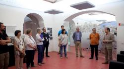 10 persones situades en una sala escolten atentament les explicacions del guia de la visita. Al fons de la sala s'observen dues arcades que embelleixen l'espai i li donen més amplitud.