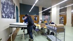 Diverses persones consulten fotografies assegudes en taules o dretes en una taula alta amb llum per poder visionar negatius i plaques de vidre
