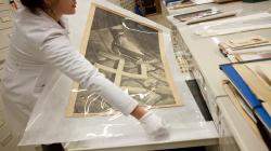 Una noia amb bata blanca i guants desa un cartell amb una foto antiga dins d'un armari planer