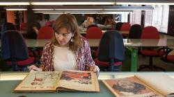Varias personas sentadas en la sala de consulta de un archivo revisando documentación