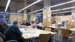 Un grup de persones assegudes en taules consulten diversos documents