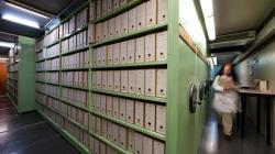 Una persona camina al costat d'una fila d'armaris compactes en una sala de dipòsit