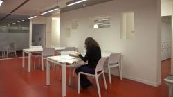 Una persona asseguda en una taula consulta documents en una sala blanca amb una altra taula més