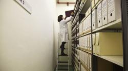 Una persona dalt d'una escala col·loca una caixa en una prestatgeria plena de caixes