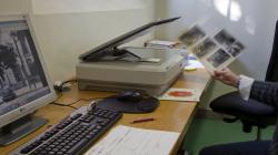 Sobre una taula hi ha un escàner i una pantalla i teclat d'ordinador, l'escàner té la tapadora alçada i es veuen diverses fotos col·locades sobre la pantalla i una mà amb un paper amb fotos adherides