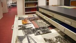 Un armari planer amb un calaix obert a dins del qual es veuen diverses fotografies, de diverses mides i en blanc i negre i color