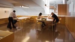 Dues persones assegudes en una taula consulten documents mentre que en una altra taula una persona dreta parla amb una altra que està asseguda