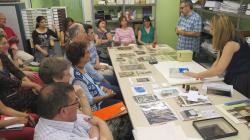 Muchas personas sentadas escuchan las explicaciones de dos personas que tienen delante una mesa llena de fotografías antiguas