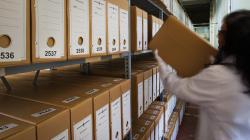 Una persona col·loca una caixa en una prestatgeria plena de caixes