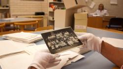 Primer pla d'unes mans amb guants que aguanten una fotografia d'època d'un grup de nens a sobre d'una taula plena de papers i dues caixes