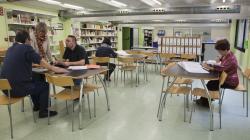 Una sala amb taules, prestatgeries plenes de llibres i dues  persones assegudes a les taules consultant documents mentre altres dues escolten les explicacions de l'arxivera