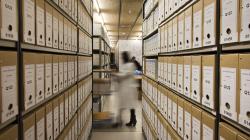 Vista d'una sala de dipòsit de l'Arxiu Municipal del Districte de Ciutat Vella, amb prestatgeries plenes de caixes i dues persones treballant