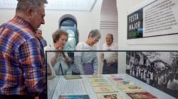 Varias personas miran una vitrina que expone programas de la fiesta mayor de Sants