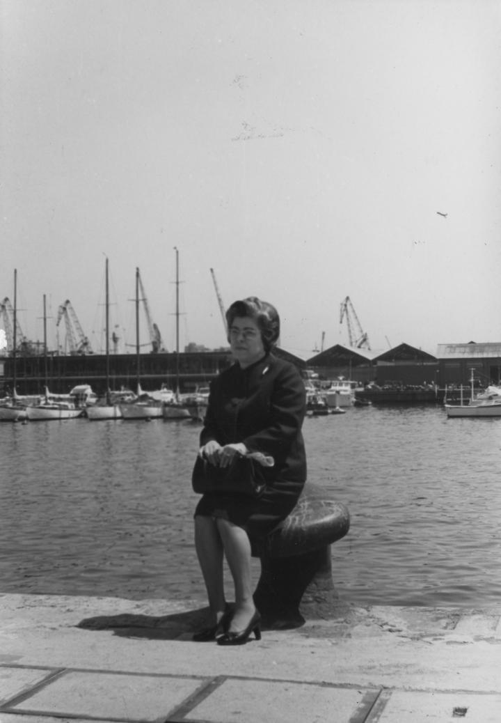 Dona asseguda al moll
