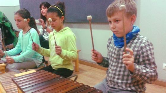 Nens i nenes de l'escola Mediterrània realitzant els tallers musicals  a Xamfrà