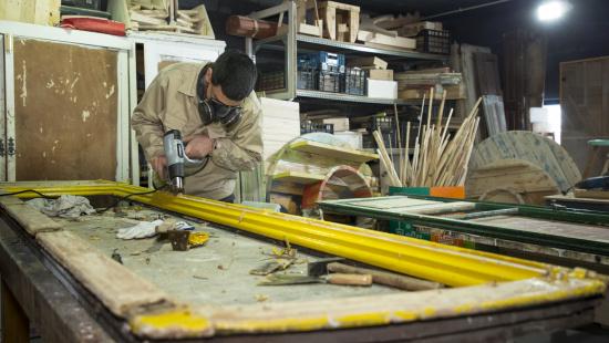 Un treballador treu la capa de pintura de la porta d'una finestra que es convertirà en un mirall