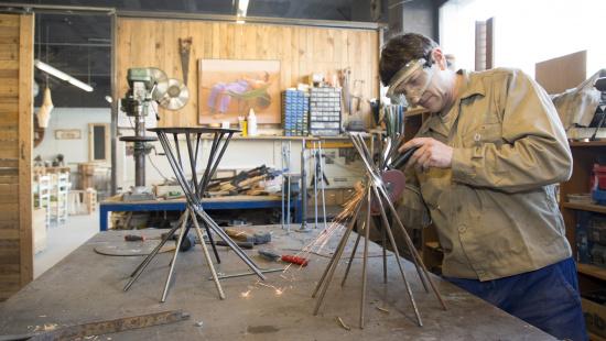 Un dels treballadors de la cooperativa solda els elements d'una peça de mobiliari