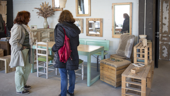 Dues clientes miren les peces de mobiliari en exposició a L'Estoc