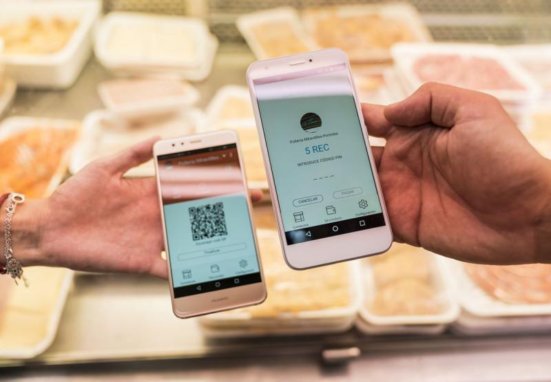 dues persones utilitzen la moneda ciutadana Rec amb els seus mòbils.