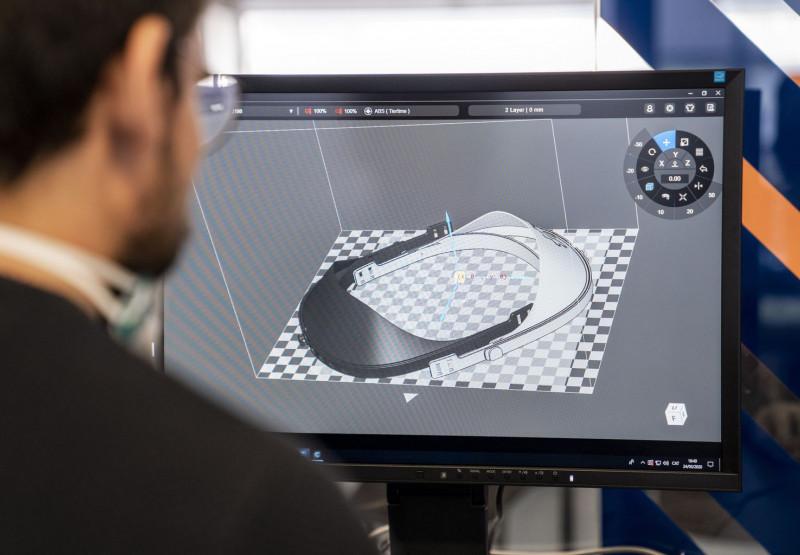 Un home executa a l'ordinador el programa perquè la impressora 3D fabriqui una visera de protecció contra la covid