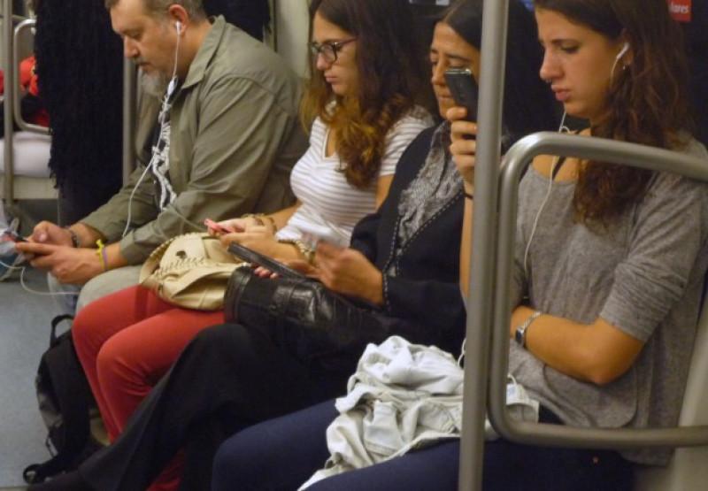 Usuaris del metro utilitzant dispositius mòbils.