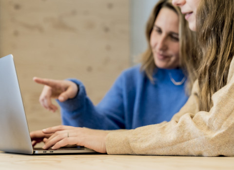 Two women interact with a laptop