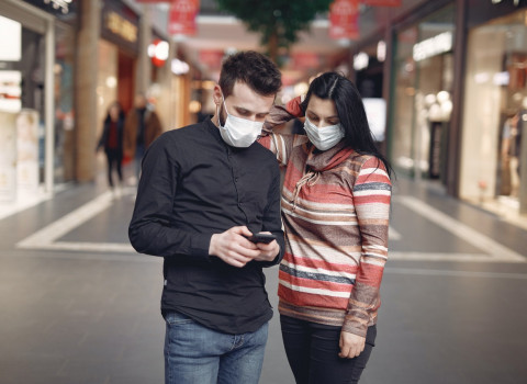 Two young people in masks consult their mobile phones in a shopping center.