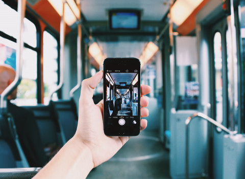 One hand holds a cellphone inside an empty bus