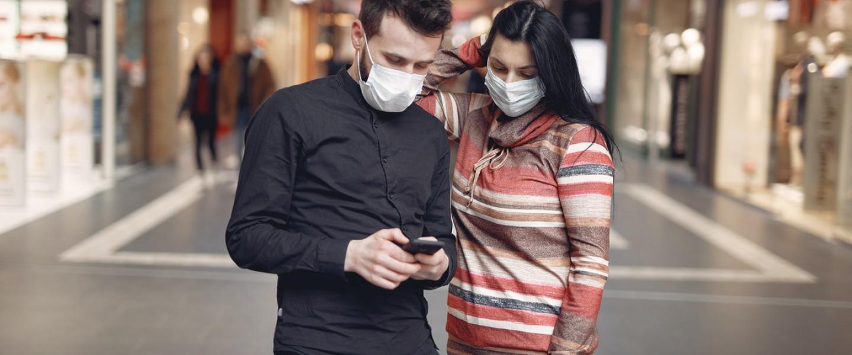 Dos jóvenes con mascarillas consultan el teléfono móvil en un centro comercial.