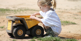 photograph of a girl with a toy truck