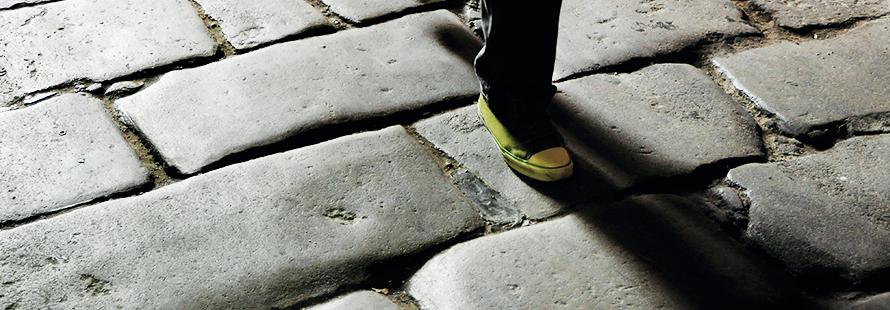 adoquines de una calle con un pie que aparece caminando